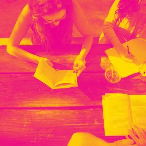 Personer sitter vid bord och läser